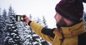 Selfie tid för en ung karismatisk turist i berget grundar den fantastiska snöig skogen, och mycket upprymt ta bilder arkivfilmer