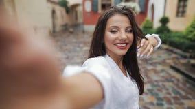 Selfie Tid Stående av den unga attraktiva kvinnan som poserar på kameran med olik sinnesrörelse i stadsgatan close upp stock video