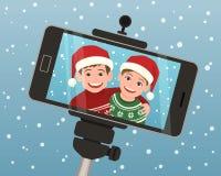 Selfie tillfångatagande av två ungar för att hälsa för jul Royaltyfri Fotografi