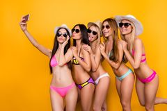 Selfie time, babes! Five girlfriends in swim suits, sunglasses a. Nd caps are posing for a selfie photo, that asian lady is taking. They are embracing, making stock photos