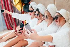 Selfie time bathrobe girls fun relaxation habit. Selfie time. Bathrobe girls taking mobile photography. Fun and relaxation habit. Sunglasses and towel turbans on stock photo