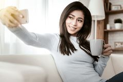 Pretty longhaired young woman posing on camera. Selfie time. Charming brunette expressing positivity while going to drink tea stock image