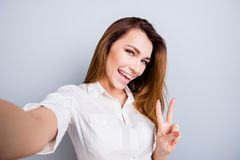Selfie time! Funky mood. Attractive young lady is making a selfie on the camera, flirty and playful. Gesturing v sign, standing o. N pure light grey background royalty free stock image