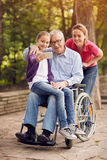 Selfie time- granddaughter, daughter and disabled man in wheelch. Selfie time in the park - granddaughter, daughter and disabled men in wheelchair Stock Images