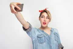 Selfie time! Portrait of happy attractive blogger woman in casual blue denim shirt with makeup, red headband standing, holding. Phone and making selfie. indoor stock photo