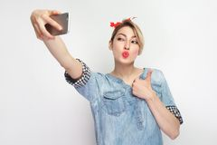 Selfie time! Portrait of sexy attractive blogger woman in casual blue denim shirt with makeup, red headband standing, holding. Phone and making selfie, showing stock image