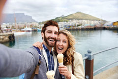 Selfie travel couple. Couple eating icecream taking selfie on holiday vacation travel Stock Images