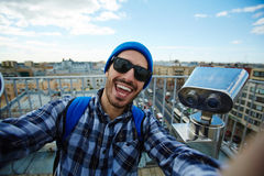 Selfie on travel. Smiley man in eyeglasses making selfie on background of cityscape royalty free stock image