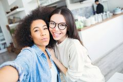 Selfie of two beautiful friends standing together. Afro american is holding a phone in her hands while the other one is royalty free stock photography