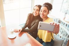 This is a selfie of two beautiful girls that look so amazing and happy at the same time. They are in cafe drinking some stock photos
