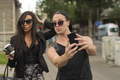 Selfie - Two cheerful friends taking photos of themselves on smart phone royalty free stock images