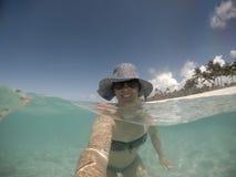 Selfie uśmiechnięta w średnim wieku kobieta w kapeluszu i cienie w morzu a fotografia royalty free