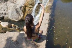 Selfie ung flicka som utomhus tar smartphonebilden av vattenfallet Royaltyfri Fotografi