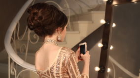 Selfie Ung tonårs- flicka som tar fotoet i guld- klänning och smycken Elegant dam i paljettklänningen som poserar vid spegeln med lager videofilmer