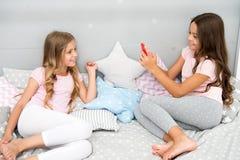 Selfie van modellering van jonge geitjes - twee meisjes die selfie op smartphone maken meisjesjonge geitjes die in slaapkamer mod stock foto
