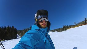 Selfie video of extreme young man riding snowboard, winter vacation in mountains. Stock footage stock footage