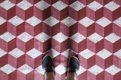 Selfie von Füßen mit Turnschuhschuhen auf rotem und weißem Würfel 3d des Kunstmuster-Fliesenbodens Stockfoto