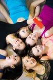 采取selfie,自画象w的小组愉快的运动的女朋友 库存照片