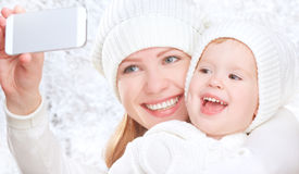 Selfie  in winter. happy family mother with daughter and photographed self on  mobile phone Royalty Free Stock Photo