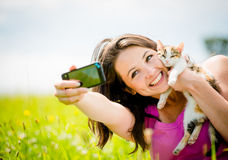 Selfie woman and cat. Woman taking photo with mobile phone camera of herself and her cat - outdoor in nature Stock Photo