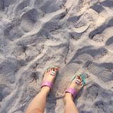 Selfie of woman feet wearing flip flops on a beach Royalty Free Stock Images