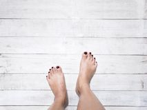 Selfie woman feet on wood background. royalty free stock image