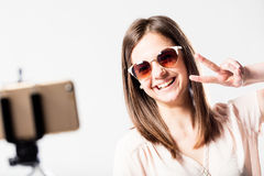 Selfie woman with selfie stick and victory. Happy woman taking herself a selfie with his smartphone and a selfie stick with the victory sign Royalty Free Stock Photography