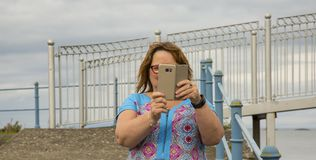 Selfie woman with smart phone. Lady taking a selfie with smart phone Stock Image