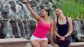 Selfie women. Two young women taking selfie near waterfall. Women selfie. Selfie photo. Selfie girls. Funny women taking photo with phone in park. Cheerful stock footage