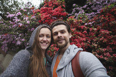 Selfie of a young beautiful couple on the background bright pink and red flowers. Couple smiling. Royalty Free Stock Photos