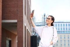 Selfie. Young beautiful girl is making herself a photo by smartphone royalty free stock photo