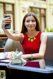 Selfie, Young beautiful girl photographed on a cell phone. In coffee shop Stock Images