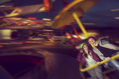 Selfie. Young couple in love having fun and taking selfie while riding on merry go round in an amusement park Royalty Free Stock Photo