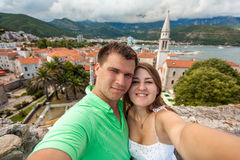 Selfie of young couple in love posing against old city of Budva Stock Photography