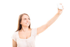 Selfie. Young girl making a photograph of herself isolated on white background Stock Images
