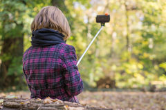 Selfie. Young girl taking picture with smartphone selfie stick from back Royalty Free Stock Images