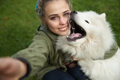 selfie of a young woman in green coat and multicolored dreadlocks with his white Samoyed dog in the autumn Park stock photo