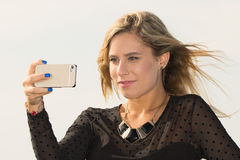 Selfie. A young woman taking a picture with his cell phone selfie Stock Image