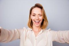 Selfie-Zeit! Schließen Sie oben von attarctive junger blonder Dame in einer Beige Stockfoto