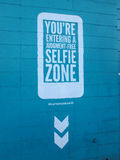 Selfie Zone. HONOLULU - AUGUST 20:  'You're Entering A Judgement-Free Selfie Zone' Sign on blue wall with hashtag talking about the latest crazes in America on Stock Photos