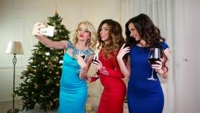 Selfiefoto för nytt år gör en flicka, den härliga unga kvinnan som firar jul på ett parti, mobiltelefon i handflicka stock video