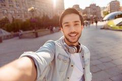 Selfiemanie! De opgewekte jonge kerel maakt selfie op een camera Hij royalty-vrije stock fotografie