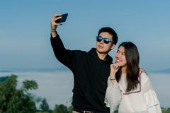 A couple who are lovers on dating take selfies together by smartphone with top view of the hill in the backgroud. An asian adolesc. Couple who are lovers on royalty free stock images