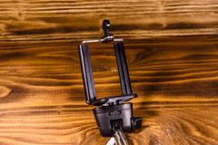 Selfiestok met regelbare klem op een houten lijst stock afbeelding