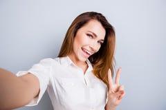 Selfietijd! Funky stemming De aantrekkelijke jonge dame maakt een selfi royalty-vrije stock afbeelding
