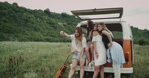 Selfietijd in het midden van gebied, groep jonge dames die beelden nemen die in de rug van een retro bestelwagen zitten stock video