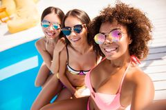 Selfietijd, meisjes! Drie charmante meisjes in modieus Di stock fotografie