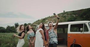 Selfietijd voor groep vrienden, die nemend beelden in het midden van gebied, erachter van hun retro bestelwagen 4K stock footage