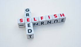 Selfish and greed. Text ' selfish ' and ' greed ' inscribed in uppercase letters on small white cubes and presented crossword style with common letter ' e ' Stock Image