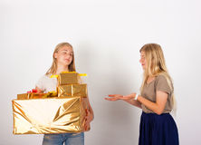 Selfish sister at christmas. I don't give from my presents to you - Selfish girl doesn't share her gift boxes with her sister stock image